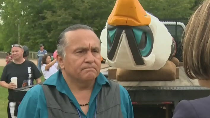 Jewell James of Washington state's Lummi Nation  stands in front of the totem pole he spent five months carving.