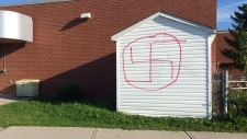 Spray-painted swastika on shed at school