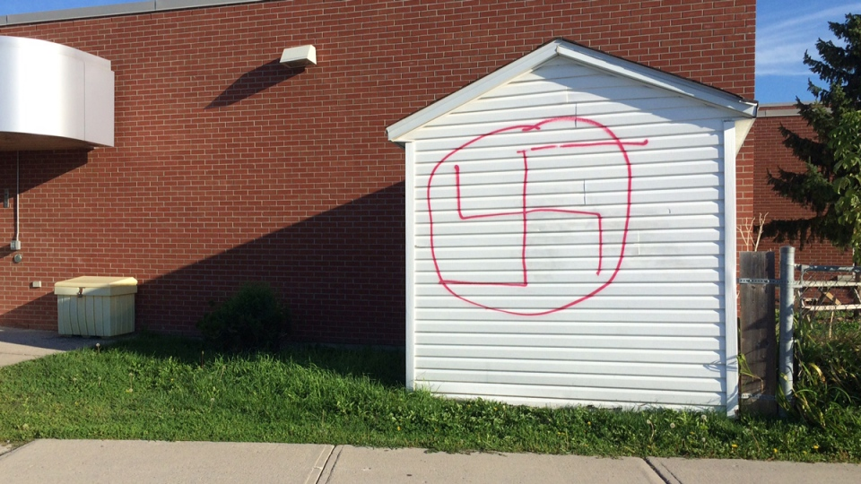 Ottawa Police are investigating after vandals sprayed a hateful symbol on the side of a shed at St. Theresa Catholic Elementary School over the weekend. (Allison Sandor/CFRA)