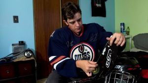 Jesse Thompson, 17, tapes his hockey stick in his room in Oshawa, Ont., on Monday, September, 15 2014. Thompson is a transgender hockey player who fought for his rights against Hockey Canada. (Nathan Denette/The Canadian Press)