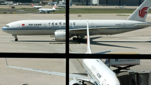 In this Sept. 5, 2013 file photo, an Air China's Boeing 777 jet, top, taxis to a gate after landing at Beijing International Airport in Beijing, China. (AP Photo/Alexander F. Yuan)