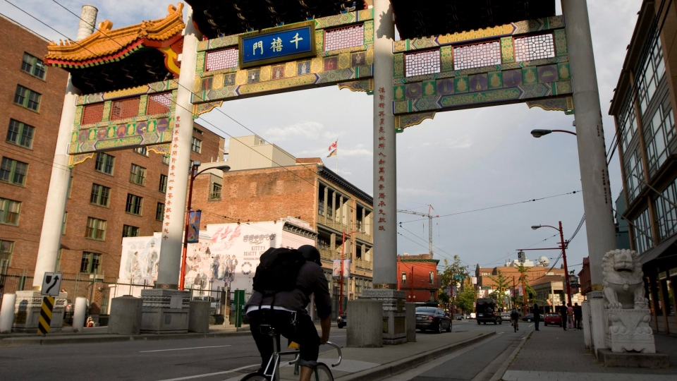 A cyclist rides his bike into Chinatown in downtown Vancouver, B.C. Tuesday, Sept. 1, 2009. THE CANADIAN PRESS/Jonathan Hayward
