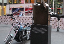 A motorcycle sits next to a piece of steel beam from the south tower