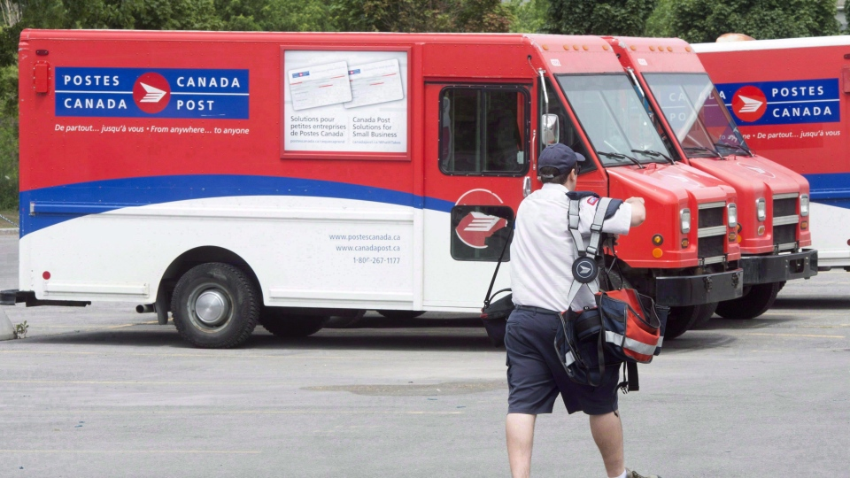 A postal worker walks past Canada Post trucks at a sorting centre in Montreal on July 8, 2016. (THE CANADIAN PRESS/Ryan Remiorz)