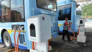 A driver charges an electric bus made by King Long United Automotive Industry at a terminal in Lin'an city in eastern China's Zhejiang Province on Friday, July 15, 2016. (Chinatopix)