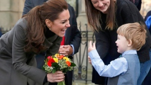 The Duchess of Cambridge receives flowers from three-year old Theo Hayward, as she leaves the GISDA centre in Caernarfon, North Wales, Friday Nov. 20, 2015. (Phil Noble / PA via AP)