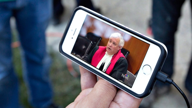 A member of the media watches Court of Queen's Bench Justice Denny Thomas make his decision in the Travis Vader case on Sept. 15, 2016. (Jason Franson / THE CANADIAN PRESS)