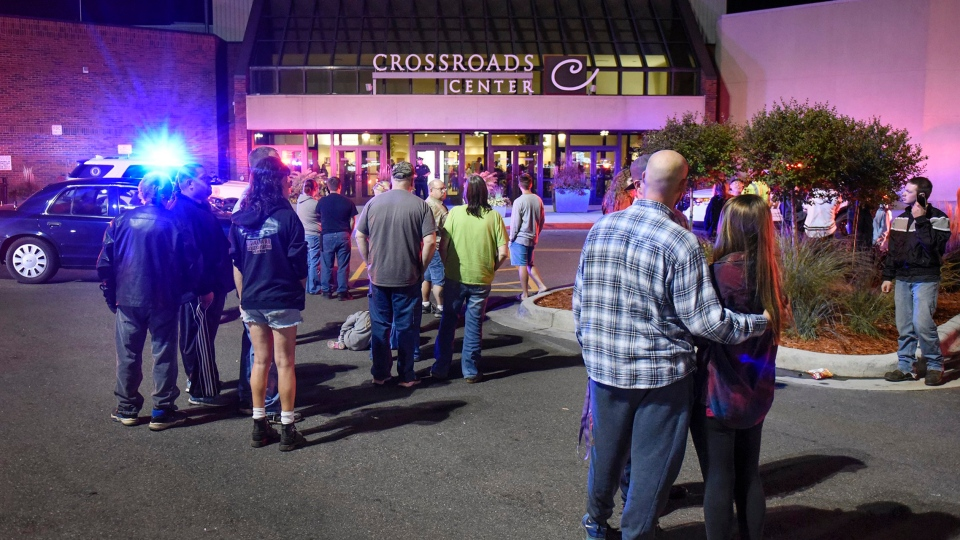 People stand near the entrance on the north side of Crossroads Center shopping mall in St. Cloud, Minn., Saturday, Sept. 17, 2016. Several people were taken to a hospital with injuries after a stabbing attack at the mall, which ended with the suspected attacker dead inside the mall. (Dave Schwarz/St. Cloud Times)