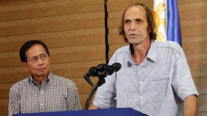 "A Norwegian man freed by militants after a year of jungle captivity in the southern Philippines described the ordeal Sunday as ""devastating,"" carrying a backpack with a bullet hole as a reminder of a near-death experience that included the beheadings of the two Canadians kidnapped with him. (Manman Dejeto/AP)"