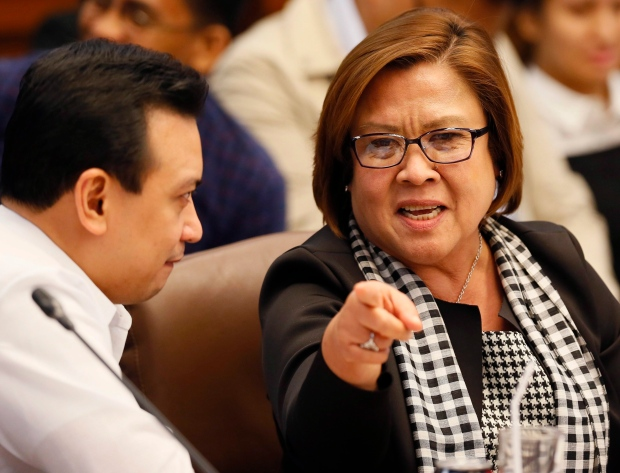 Senator Leila De Lima, right, gestures as she talks to fellow Senator Antonio Trillanes IV at the continuing Senate probe on the rising number of extrajudicial killings related to Philippine President Rodrigo Duterte's 'War on Drugs' Tuesday, Aug. 23, 2016 in suburban Pasay city south of Manila, Philippines. (AP Photo/Bullit Marquez)