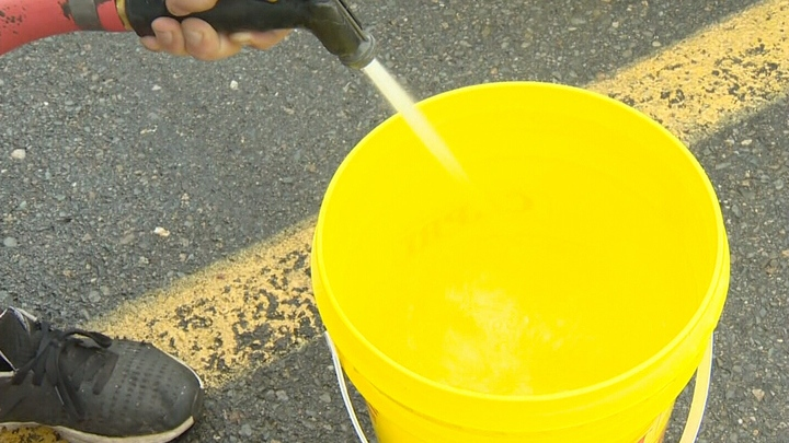 Residents of Shelburne, N.S. fill buckets of water at the local fire station.
