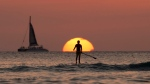 In this Tuesday, Dec. 31, 2013, file photo, a paddleboarder looks our over the Pacific Ocean as the sun sets off of Waikiki Beach, in Honolulu. (Carolyn Kaster/AP)