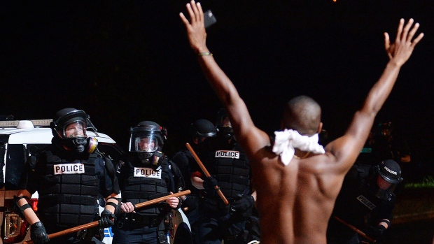 A protester raises his arms in front of officers in Charlotte, N.C., Tuesday, Sept. 20, 2016. Authorities used tear gas to disperse protesters in an overnight demonstration that broke out Tuesday after Keith Lamont Scott was fatally shot by an officer at an apartment complex. (Jeff Siner / The Charlotte Observer via AP)