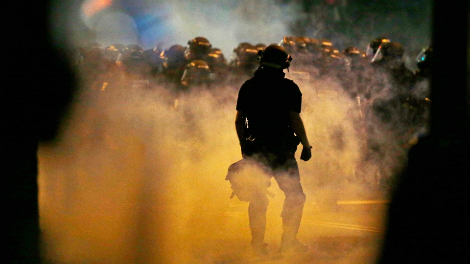 Police fire teargas as protestors converge on downtown following Tuesday's police shooting of Keith Lamont Scott in Charlotte, N.C., Wednesday, Sept. 21, 2016. (AP Photo / Gerry Broome)