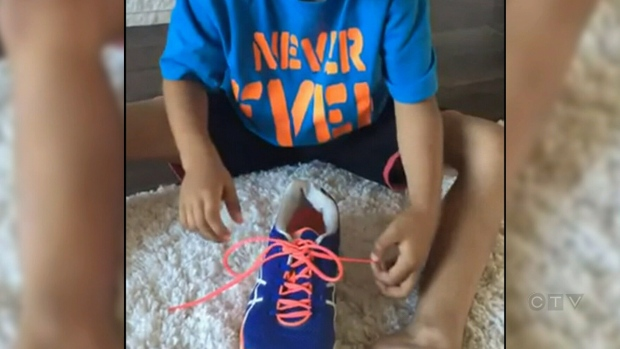 Six-year-old Rylan finishes tying a pair of shoes using his mom's modified double-knot technique. (Youtube)