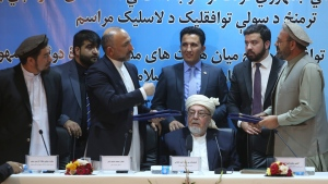 Amin Karim, representative of Gulbuddin Hekmatyar, right, and Afghanistan national security adviser Mohammad Hanif Atmar, third left, after signing a peace deal in Kabul, Afghanistan, on Sept. 22, 2016. (Rahmat Gul / AP)