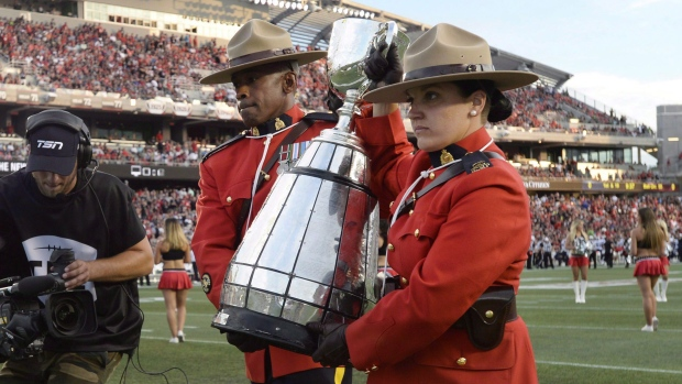 RCMP officers carry the Grey Cup as Ottawa is announced as the host of the 2017 Grey Cup championship, before CFL action between the Ottawa Redblacks and the Toronto Argonauts, in Ottawa on Sunday, July 31, 2016. (Justin Tang/The Canadian Press)