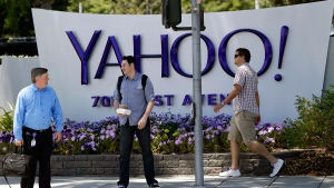 In this June 5, 2014, file photo, people walk in front of a Yahoo sign at the company's headquarters in Sunnyvale, Calif. Stocks were slightly lower in afternoon trading Friday following three straight days of gains this week. Technology stocks were trading heavily, particularly Facebook, Yahoo and Twitter. Energy stocks fell with the price of oil. (AP / Marcio Jose Sanchez)