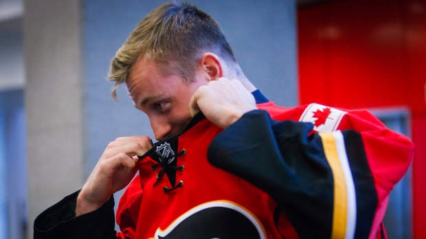 Calgary Flames' Daniel Pribyl, from the Czech Republic, pulls off his jersey after a photo session prior to the start of training camp in Calgary, Thursday, Sept. 22, 2016. (THE CANADIAN PRESS / Jeff McIntosh)