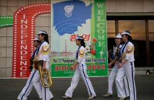 North Korean band members who performed at the Pyongyang International Film Festival walk past a sign at the venue where it was held, on Friday, Sept. 23, 2016, in Pyongyang, North Korea. (AP Photo/Wong Maye-E)