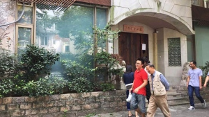 People walk past the closed Taian Table restaurant in Shanghai on September 23, 2016. A Shanghai restaurant has closed down just a day after being awarded a coveted star in the Michelin guide's first mainland Chinese edition. (DEBORAH LU / AFP)