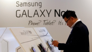 "A man tries on Samsung Electronics' new device Galaxy Note, which features the 5.29"" Super Amoled screen and runs on the Android 2.3 during its unveiling ceremony in Seoul, South Korea, Monday, Nov. 28, 2011.(AP Photo/Lee Jin-man)"