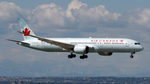 A Boeing 787 (787-9) Dreamliner jet, belonging to Air Canada, lands in Calgary, Alberta on Aug. 4, 2016. The Rocky Mountains are in the distance. THE CANADIAN PRESS IMAGES/Larry MacDougal