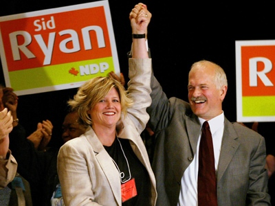 Federal NDP leader Jack Layton holds the hand of Hamilton East MPP Andrea Horwath at the CUPE Ontario convention in Toronto on Saturday, May 29, 2004.(THE CANADIAN PRESS / Andrew Vaughan)