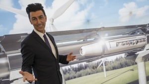 This photo taken on September 20, 2016 shows Chairman of Hyperloop Transportation Technologies Inc Bibop Gresta posing in front of a rendering of the Hyperloop technology at Innotrans, the railway industry's largest trade fair, in Berlin. (John MacDougall / AFP)