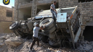In this photo provided by the Syrian Civil Defense group, rescue workers remove a destroyed ambulance outside the Syrian Civil Defense main center after airstrikes in Ansari neighborhood in the rebel-held part of eastern Aleppo, Syria, Friday, Sept. 23, 2016. (Syrian Civil Defense White Helmets via AP)