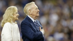 Hall of Fame Los Angeles Dodgers broadcaster Vin Scully places his hand over his heart as he is joined by wife Sandi during Vin Scully Appreciation Day before the team's baseball game against the Colorado Rockies in Los Angeles on Friday, Sept. 23, 2016. (AP / Jae C. Hong)