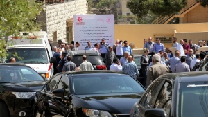 An ambulance transports the body of Jordanian writer Nahed Hattar to a medical facility, after he was shot, in Amman, Jordan, Sunday, September 25, 2016. (AP Photo/Raad Adayleh)
