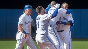 Toronto Blue Jays Edwin Encarnacion (right) is mobbed by teammates (left to right) Josh Donaldson, Kevin Pillar and Ezequiel Carrera after he drove in the winning run in the ninth inning of their American League MLB baseball game against the New York Yankees in Toronto, Sunday, September 25, 2016. (Fred Thornhil/The Canadian Press)