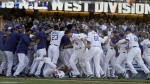 Members of the Los Angeles Dodgers celebrates after winning NL West division with a 4-3 viceroy over the Colorado Rockies in the 10th inning of a baseball game in Los Angeles, Sunday, Sept. 25, 2016. (AP / Chris Carlson)