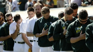 Members of the Oakland Athletics observe a moment of silence in memory of Miami Marlins pitcher Jose Fernandez, who died in a boating accident early Sunday, before a baseball game against the Texas Rangers Sunday, Sept. 25, 2016, in Oakland, Calif. (AP / Marcio Jose Sanchez)