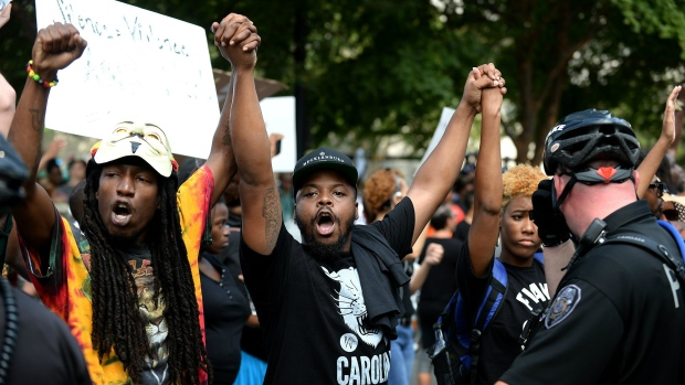 Protesters chant slogans as police officers stand nearby at Bank of America Stadium in Charlotte, N.C., Sunday, Sept. 25, 2016. (Jeff Siner/The Charlotte Observer via AP)