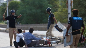"In this Sunday, Aug. 31, 2014 file photo, Pakistani police officers baton charge motorcyclists in Islamabad, Pakistan. Human Rights Watch says Pakistan's corrupt and ill-equipped police system encourages serious rights violations, including arbitrary arrests, torture and ""encounter killings"" in which police stage shootouts to kill individuals in custody. (B.K. Bangash/AP)"