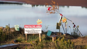 Conflicting signs are posted near the Shubenacadie River in Fort Ellis, N.S. on Monday, Sept. 26, 2016. (Andrew Vaughan / THE CANADIAN PRESS)