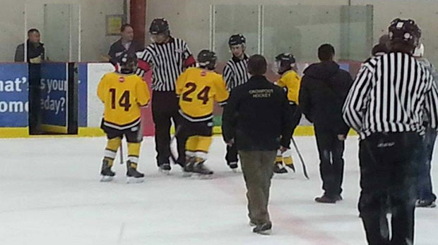 Griffin White, number 24, shakes hands with an official at a peewee game in Calgary.