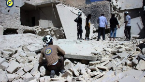 This photo provided by the Syrian Civil Defense group known as the White Helmets, shows members of Civil Defense inspecting damaged buildings after airstrikes hit the Bustan al-Qasr neighborhood of Aleppo, Syria, Sunday, Sept. 25, 2016.  (Syrian Civil Defense White Helmets via AP)