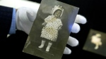 Martin Nolan, Executive Director of Julien's Auctions, holds a photograph of actress Marilyn Monroe at age 2 during an exhibition of Monroe's personal effects in Beijing, Tuesday, Sept. 27, 2016. (AP / Mark Schiefelbein)