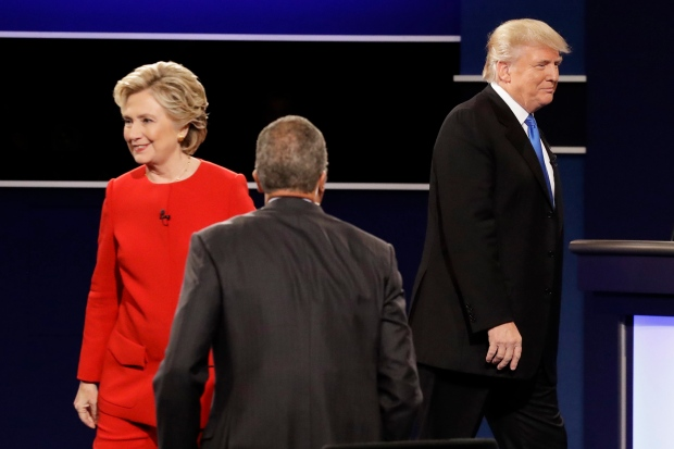 Democratic presidential nominee Hillary Clinton and Republican presidential nominee Donald Trump walk their separate ways after the presidential debate at Hofstra University in Hempstead, N.Y., Monday, Sept. 26, 2016. (AP Photo/David Goldman)