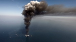"This file photo shows a large plume of smoke rising from BP's Deepwater Horizon offshore oil rig in the Gulf of Mexico on April 21, 2010. The film, ""Deepwater Horizon"" is stirring mixed emotions for family members of the 11 men who died in the blast. (AP Photo/Gerald Herbert, File)"