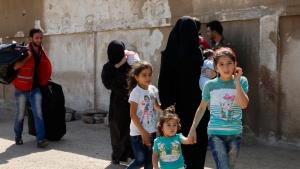 Women accompanied by their children prepare to leave Al-Waer, the last rebel-held neighborhood of Homs, Syria, Thursday, Sept. 22, 2016. (AP Photo)