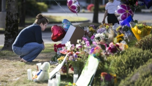 Rachel Shuler of Burlington, Wash., takes a moment after placing a sign and balloons with her stepdaughter at a makeshift memorial  in Burlington, to the victims the victims killed in a mall shooting on Friday, in this photo taken on Sunday, Sept. 25, 2016. (AP / Stephen Brashear)