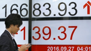 A man uses a mobile phone in front of an electronic stock indicator of a securities firm in Tokyo, Tuesday, Sept. 27, 2016. (AP / Shizuo Kambayashi)