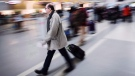 A man carries his luggage at Pearson International Airport in Toronto on December 20, 2013. Air Canada and WestJet are facing a potential class action lawsuit after imposing checked baggage fees only days apart. THE CANADIAN PRESS/Mark Blinch