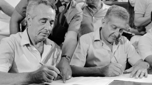 In this Aug. 22, 1984, file photo, Israel's Prime Minister designate Shimon Peres and former defense minister Ezer Weizman sign an agreement between their two parties in Tel Aviv. (AP Photo/cGivon, File)
