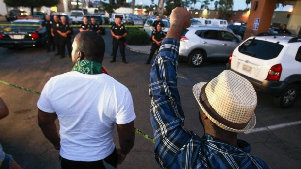 One man holds his fist up as others yell at police at the scene where a black man was shot by police earlier in El Cajon, east of San Diego, Calif., Tuesday, Sept. 27, 2016. (Hayne Palmour IV / The San Diego Union-Tribune)