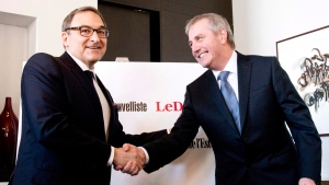 Martin Cauchon, owner of the Groupe Capitales Media, and Claude Gagnon, president and director general, shake hands after they announced the purchase of six newspapers that were owned by Gesca, Wednesday, March 18, 2015 in Quebec City. (Jacques Boissinot/THE CANADIAN PRESS)